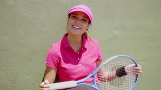 Laughing tennis player holding racket on her knees while crouched up against a green wall and wearing a bright pink visor