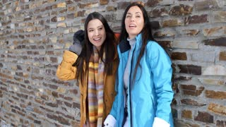 Laughing twins in jackets and glove near wall