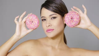 Laughing vivacious young woman holding two iced pink donuts to her eyes close up head and shoulders over grey