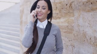 Laughing woman in sweater near wall on phone