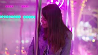 Laughing woman relaxing at a fairground standing in a brightly lit stall with pink strip lights grinning happily at the camera