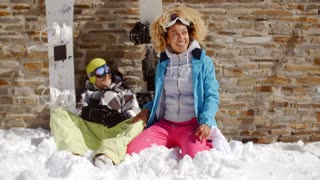 Laughing woman sitting next to friend in snow