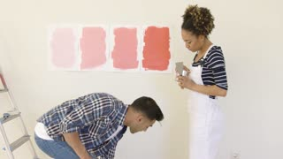 Laughing young couple choosing a paint color to renovate their new house standing with a roller and brush in their hands in front of swatches on the wall.
