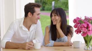 Laughing young mixed couple sitting at table with coffee cups and pink flower bouquet and copy space