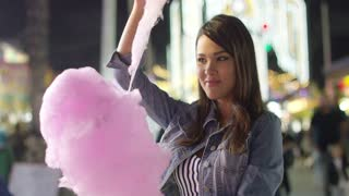 Laughing young woman eating pink candy floss pulling of a long strand of the sticky sugar with her fingers as she watches in anticipation