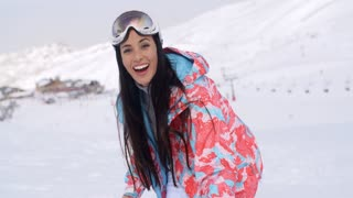 Laughing young woman throwing a snowball