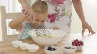 Little girl baking with her mother watching carefully as Mum whisks the ingredients in the bowl close up view