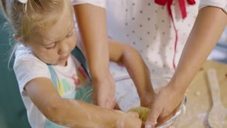 Little girl helping to knead the pastry dough while helping her mother with the baking in the kitchen close up cropped high angle view