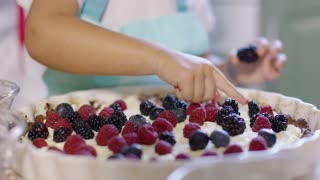 Little girl placing a fresh ripe blackberry on a freshly baked homemade berry pie topped with cream close up on her hand