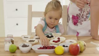 Little girl placing berries from various tiny bows on fresh muffin batter in paper cups with parent in kitchen