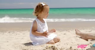 Little girl playing on a tropical beach