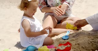 Little Girl Playing with Sand Toys at the Beach