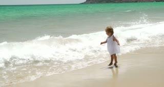 Little girl running along a beach with her mother