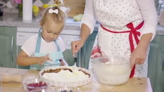 Little girl watching her mother the baking in anticipation as fresh whipped cream is added to the homemade berry pie as they work together in the kitchen.