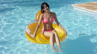 Lovely young woman floating in a swimming pool sitting on a colorful yellow tube in sexy pink bikini smiling at the camera