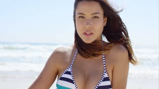 Lovely young woman in a bikini at the beach sitting with her back to the ocean looking at the camera with a pensive expression