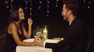 Loving young couple enjoy a romantic dinner seated at a table in an upscale restaurant or nightclub holding hands and chatting