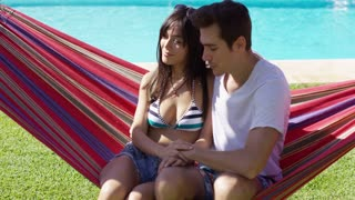 Loving young couple sitting on a hammock near a swimming pool holding hands with a handsome man looking affectionately at a pretty trendy young woman