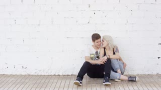 Loving young urban couple sitting in a close embrace on a brick sidewalk in front of a white exterior wall with copy space