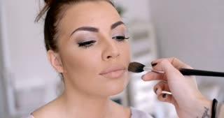 Makeup Artist Applying Lipstick to Pretty Woman