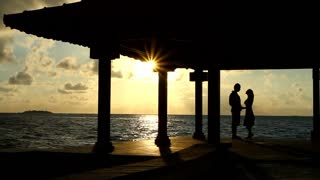 Man and Woman in Love Standing at Sunset on Sea Bridge