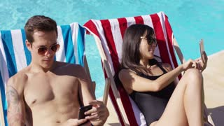 Man and woman taking self portraits with their smart phones at while seated in deck chairs at the swimming pool outside
