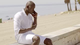 Man arguing on phone while seated on stone wall
