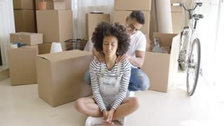 Man doing her girlfriend massage of the neck while they resting afrer exhausting work with moving to a new home