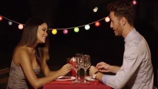Man makes flying gesture with right hand to make his dinner date laugh across red covered table