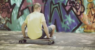 Man Sitting on Longboard and Looking Into Distance