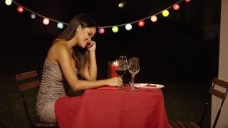 Man surprises his beautiful date with single rose at restaurant as she sits at a red covered table