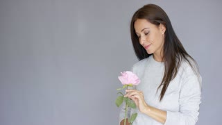Midlle aged, long haired, elegant and beautiful woman holding and smell pink rose flower. She is isolated on gray background.
