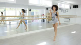 Modern african american female dancer in bright studio practicing new moves.