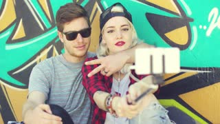 Modern fashionable young couple taking a selfie as they pose sitting together in front of a colorful graffiti covered wall