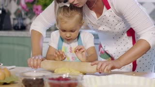 Mother rolling out pastry with a little helper as she teaches her cute little daughter bake in the kitchen