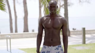 Muscular black man bares his chest near grass