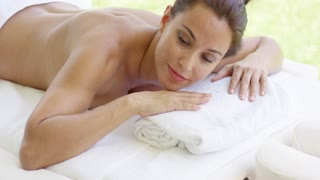 Naked woman relaxes on massage table with chin on hands over folded towel in outdoor spa