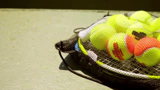 Net bag of tennis balls for training on a racket