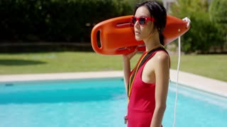 One serious beautiful young woman in red swimsuit and sunglasses holding floatation device beside pool