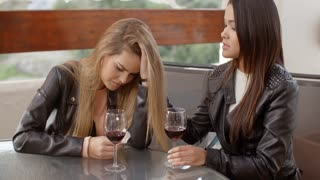 Pair of sad women drinking wine
