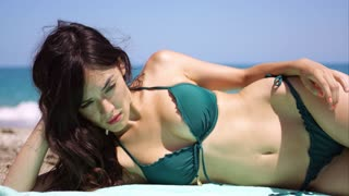 Pensive beautiful woman lying sunbathing in a bikini on a towel at the beach looking off to the side with a dreamy expression