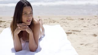 Pensive young woman sunbathing on a beach lying on her towel facing the camera with the sea behind her close up of her face