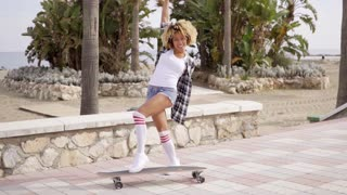 Playful sexy young woman posing with a skateboard