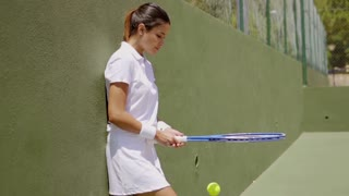 Pretty athlete practicing with ball and racket in green tennis court and wearing white outfit