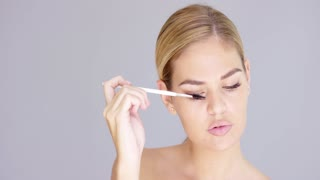 Pretty blond woman applying mascara to her eyelashes using a long handled cosmetics brush in a beauty makeup and glamour concept