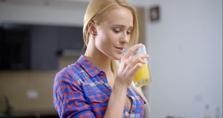 Pretty Blond Woman Drinking Juice in a Glass