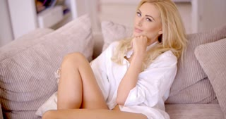 Pretty Blond Woman on Sofa Looking at Camera