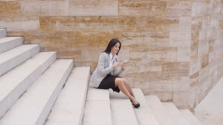 Pretty business woman sitting on steps using phone