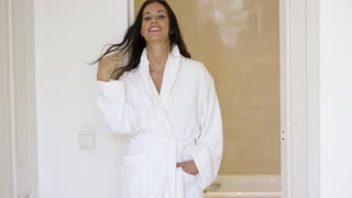 Pretty female adult in white bath robe near bathroom entrance moving hair to side with other hand in pocket