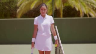 Pretty female athlete smiles at camera while holding tennis racket to her shoulder and standing near tall green wall
